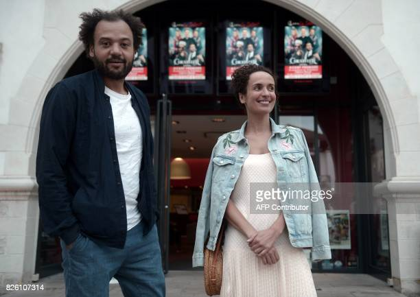 French director Fabrice Eboue and actress Amelle Chahbi pose prior to the premiere of their movie 'Coexist' in front of the theatre 'Le Select' in...