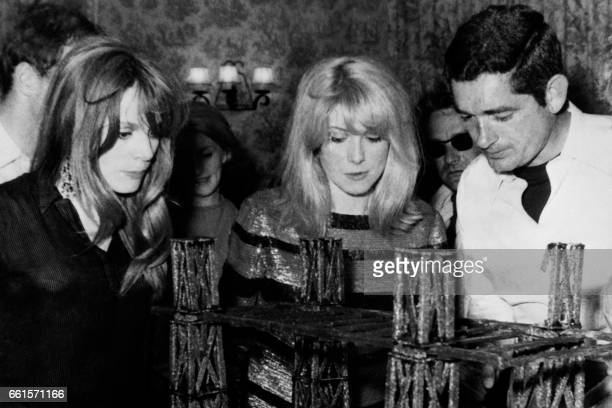 French director Jacques Demy looks at his birthday cake 'a transporter bridge' next to french actresses Francoise Dorleac and Catherine Deneuve...