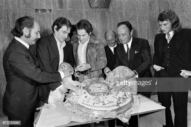 French director Jean Larriaga flanked by French actors Robert Hossein Raymond Pellegrin and French singer Johnny Hallyday gives a slice of cake to a...