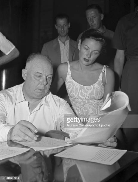 French director Jean Renoir sitting next to the actress Gene Tierney wearing embroidered dress both reading some sheets Venice 1951