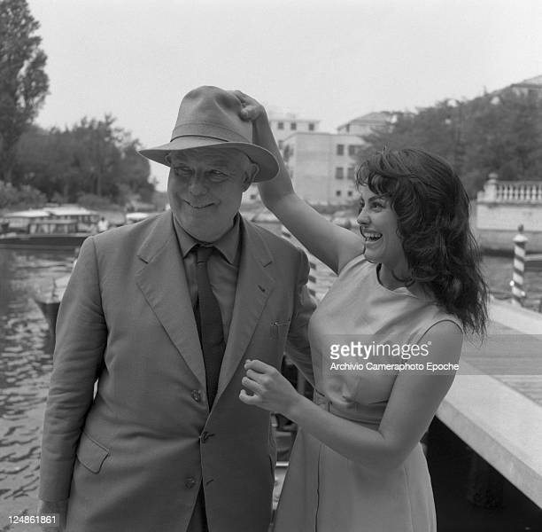 French director Jean Renoir wearing a suit a tie and a hat posing fot the photographers next to the french actress Catherine Rouvel in Lido for the...
