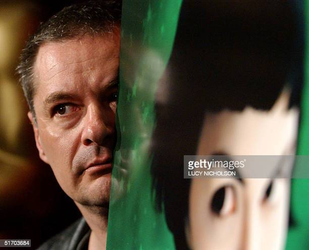 French Director JeanPierre Jeunet peers at the media from behind a poster of his film 'Amelie' at a Symposium for the directors of Oscar nominated...