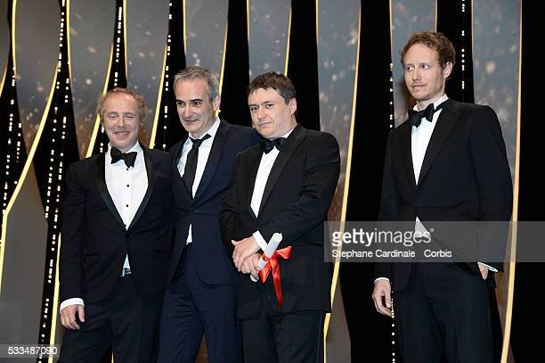 French director Olivier Assayas and Romanian director Cristian Mungiu pose on stage with members of the Jury Arnaud Desplechin Laszlo Nemes after...