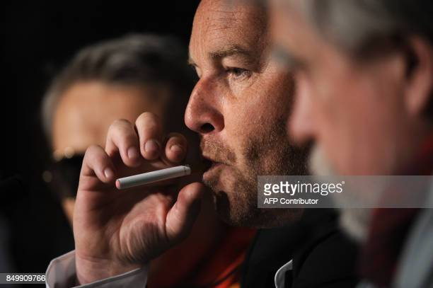 French director Xavier Beauvois smokes an electronic cigarette during the press conference of 'Des Hommes et des Dieux' presented in competition at...