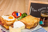 Traditional french sandwiches, croque madame and croque monsieur, fine cheese and fresh salad, placed on table and near it a chalkboard with the message of bon appetit.
