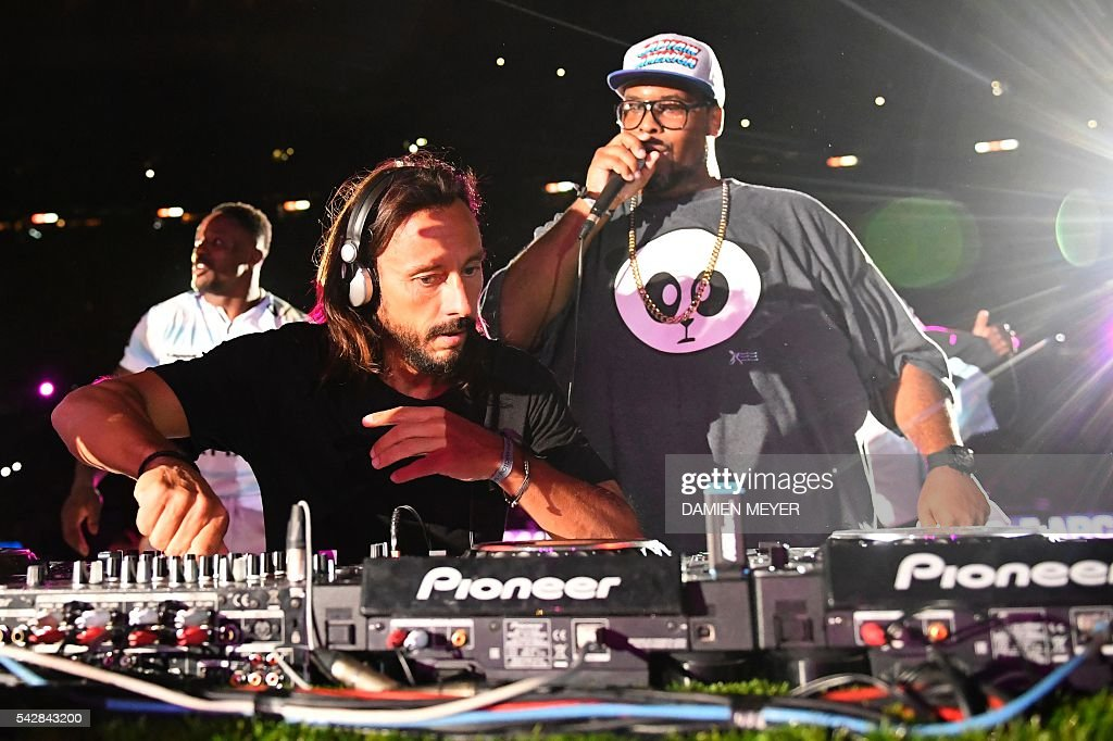 French DJ Bob Sinclar (L) mixes past US DJ Big Ali at the end of the French Top14 rugby union final match Toulon vs Racing 92 at the Camp Nou stadium in Barcelona on June 24, 2016. / AFP / DAMIEN