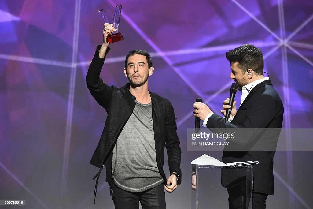 French DJ Tristan Casara aka The Avener (L), flanked by French TV host and Master of Ceremony Bruno Guillon (R), poses after receiving the best electronic music album award during the 31st Victoires de la Musique, the annual French music awards ceremony, on February 12, 2016 at the Zenith concert hall in Paris. AFP PHOTO / BERTRAND GUAY / AFP / BERTRAND GUAY