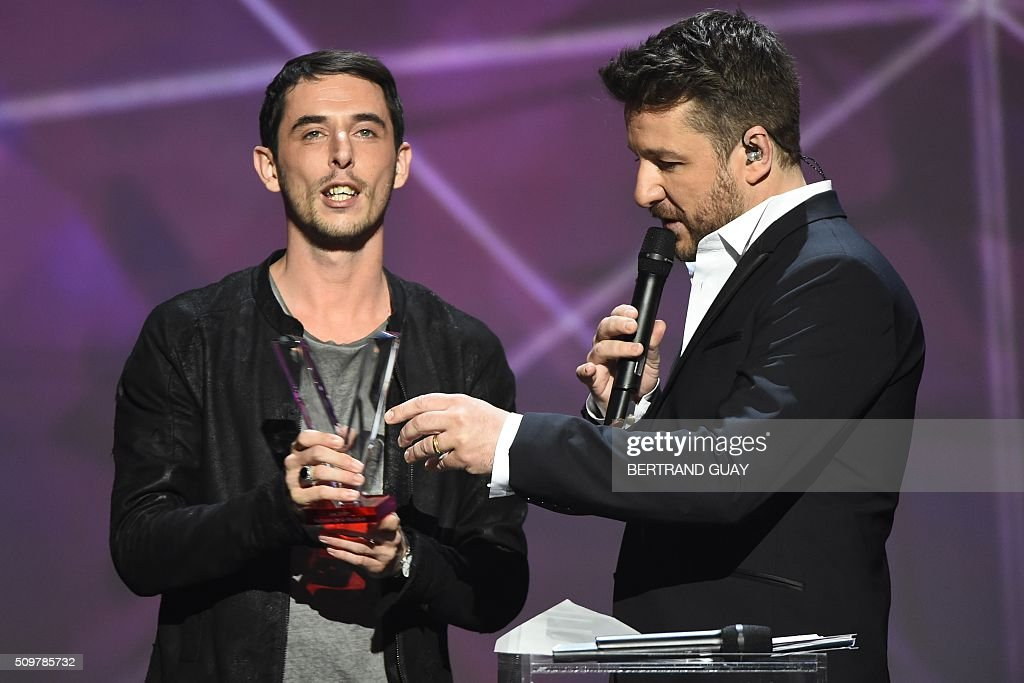 French DJ Tristan Casara aka The Avener (L), flanked by French TV host and Master of Ceremony Bruno Guillon (R), speaks after receiving the best electronic music album award during the 31st Victoires de la Musique, the annual French music awards ceremony, on February 12, 2016 at the Zenith concert hall in Paris. AFP PHOTO / BERTRAND GUAY / AFP / BERTRAND GUAY