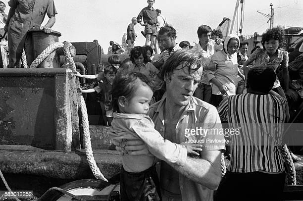 French Doctor Bernard Kouchner carries a Vietnamese refugee child on to the French hospital boat l'Ile de Lumiere, commissioned by Medecins sans Frontieres, in the South China Sea.