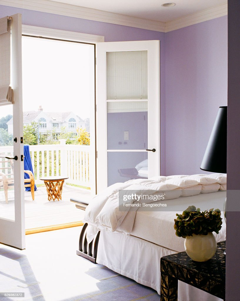 french doors in a lavender guest bedroom open onto a terrace stock photo