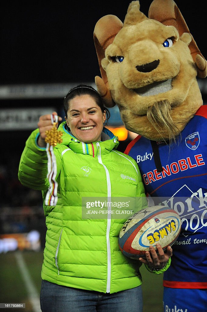 French downhill world champion Marion Rolland (L) poses with Grenoble's mascot during the kick-off of the French Top 14 rugby union match Grenoble vs Agen on February 16, 2013 at the Lesdiguieres Stadium in Grenoble, southeastern France. AFP PHOTO / Jean Pierre Clatot
