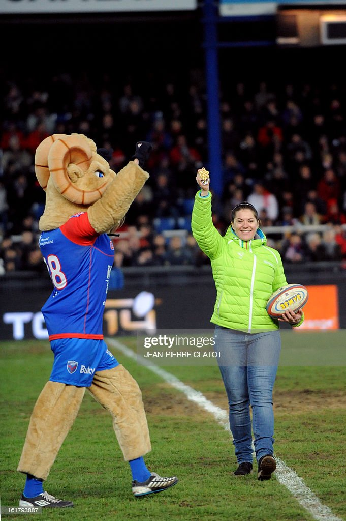 French downhill world champion Marion Rolland (R) walks on the field with Grenoble's mascot during the kick-off of the French Top 14 rugby union match Grenoble vs Agen on February 16, 2013 at the Lesdiguieres Stadium in Grenoble, southeastern France. AFP PHOTO / Jean Pierre Clatot