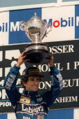 French driver Alain Prost holds his trophy after winning the German formula one Grand Prix 25 July 1993 on his William Renault AFP PHOTO/JEANPIERRE...