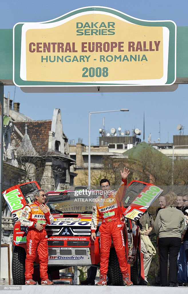 French driver Luc Alphand waves next to his copilot Gilles Picard of Repsol Mitsubishi Ralliart team on the starting podium of the Central European...