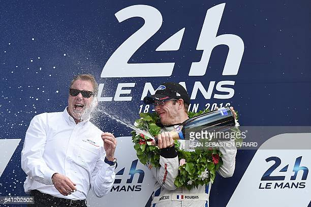 French driver Sebastien Bourdais sprays champagne onto President of Ford William Clay Ford Jr after Bourdais and fellow drivers Joey Hand of the US...