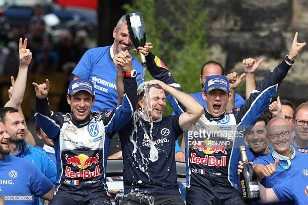 French driver Sebastien Ogier and his copilot Julien Ingrassia sit next to Volkswagen motorsport manager Jost Capito as they celebrate their victory...