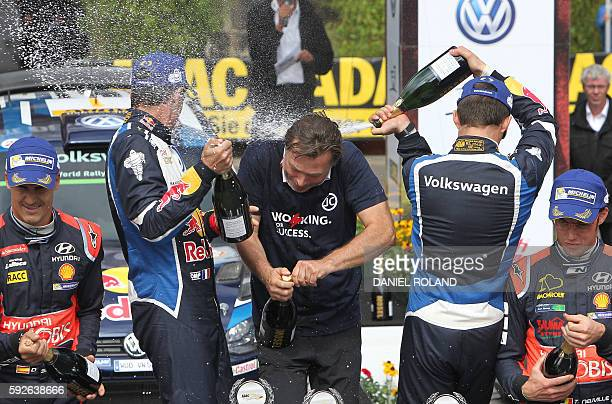 French driver Sebastien Ogier and his copilot Julien Ingrassia spray champagne onto Volkswagen motorsport manager Jost Capito as they celebrate their...