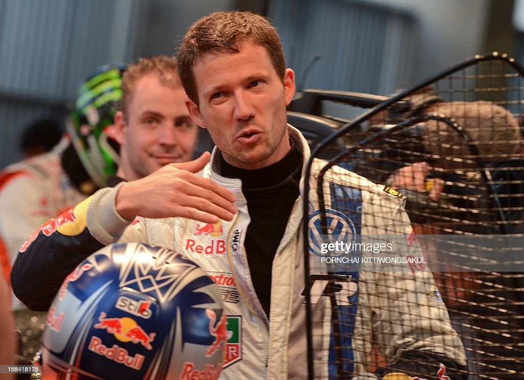 French driver Sebastien Ogier talks with staff during warm-up for the Race of Champions (ROC) at Rajamangala Stadium in Bangkok on December 16, 2012. The Race of Champions (ROC) will take place in Thailand between December 14 and 16 and brings together heavyweights from all motor racing disciplines in the same type of car.