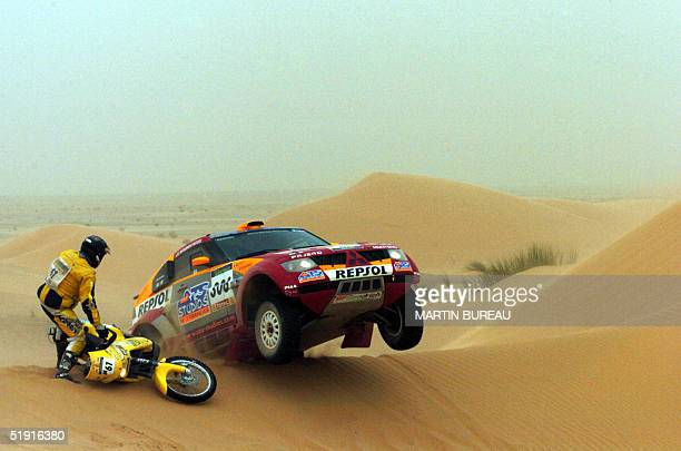 French driver Stephane Peterhansel is seen at the wheel of his Mitsubishi Pajero Evo as French KTM motorbiker Norbert Dubois looks on 05 January 2005...