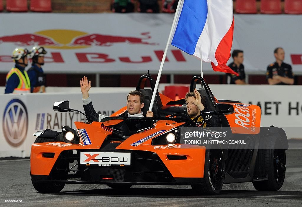 French drivers Romain Grosjean (R) and Sébastien Ogier (L) wave to fans during the Race of Champions (ROC) Nations Cup Drivers 's Presentation at Rajamangala Stadium in Bangkok on December 15, 2012. The Race of Champions (ROC) will take place in Thailand between December 14 and 16 and brings together heavyweights from all motor racing disciplines in the same type of car.