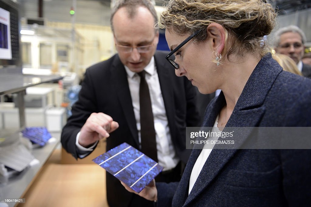 French Ecology Minister Delphine Batho observes a photovoltaic unit presented by French solar panel maker PhotoWatt Chief Executive Officer (CEO) Vincent Bes (L) as she visits on January 31, 2013 the PhotoWatt factory in Bourgoin-Jallieu, near Lyon. AFP PHOTO / PHILIPPE DESMAZES