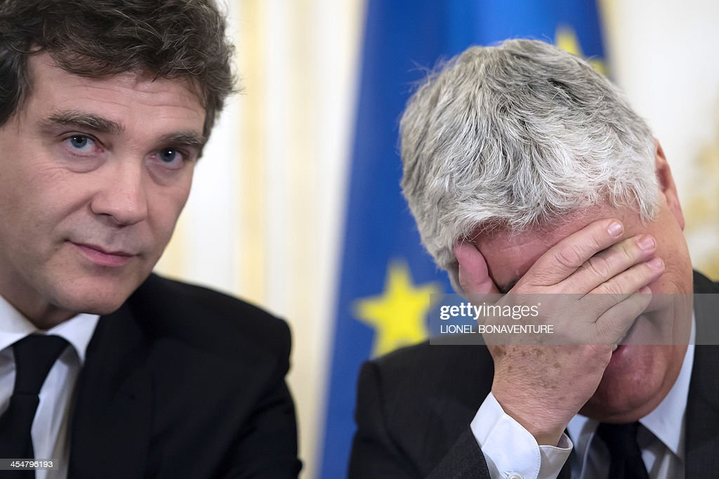 French Ecology Minister <a gi-track='captionPersonalityLinkClicked' href=/galleries/search?phrase=Philippe+Martin+-+Pol%C3%ADtico&family=editorial&specificpeople=12683642 ng-click='$event.stopPropagation()'>Philippe Martin</a> (R) laughs next to French Minister for Industrial Renewal Arnaud Montebourg during a press conference on the new mining code project on December 10, 2013 in Paris. AFP PHOTO / LIONEL BONAVENTURE