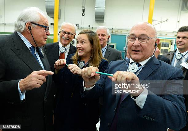 French Economy and Finance Minister Michel Sapin holds a Bic pencil flanked by Digital Sector and Innovation Junior Minister Axelle Lemaire and Bic...