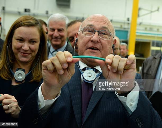 French Economy and Finance Minister Michel Sapin holds a Bic pencil flanked by Digital Sector and Innovation Junior Minister Axelle Lemaire as he...