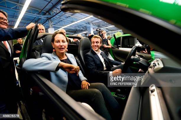 French Economy and Industry minister Emmanuel Macron and minister for Ecology Sustainable Development and Energy Segolene Royal sit in an 'SMART'...