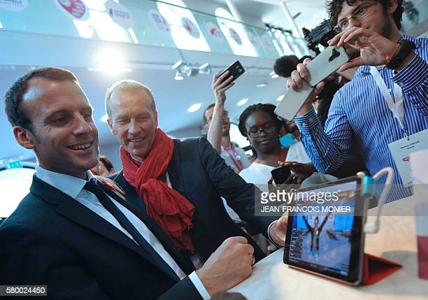 French Economy and Industry minister Emmanuel Macron flancked by Member of Parliament Guillaume Garot visit a virtual reality show on July 25 at the...
