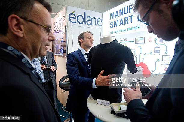 French Economy and Industry Minister Emmanuel Macron looks at a connected object as he visits the newly inaugurated 'Cite de l'Objet Connecte' in...