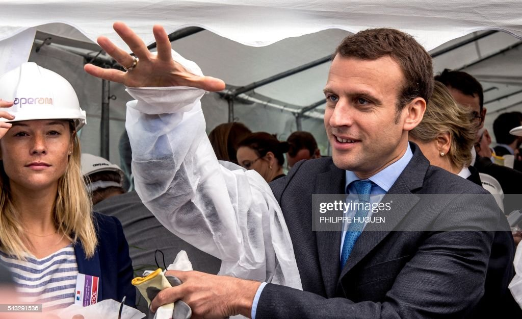 French Economy and Industry minister Emmanuel Macron puts on an overalls as he visits Aperam's stainless facilities in Isbergues, northern France, on June 27, 2016. / AFP / PHILIPPE