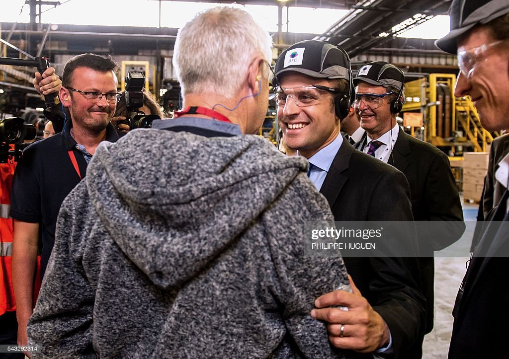 French Economy and Industry minister Emmanuel Macron salutes a worker as he visits the glass-making company Arc International in Arques, northern France, on June 27, 2016. / AFP / PHILIPPE