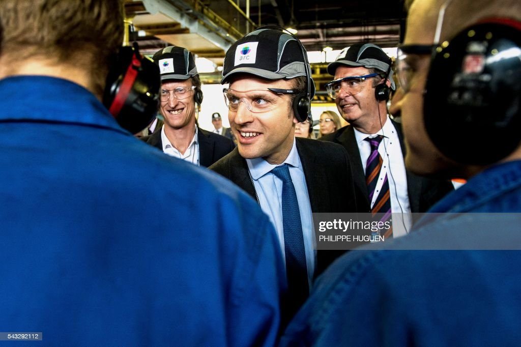 French Economy and Industry minister Emmanuel Macron salutes workers as he visits the glass-making company Arc International in Arques, northern France, on June 27, 2016. / AFP / PHILIPPE