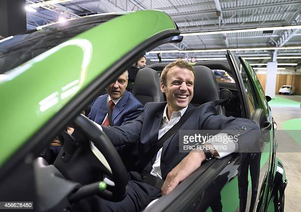French Economy and Industry minister Emmanuel Macron sits in an 'SMART' electric car displayed at the 2014 Paris Auto Show on October 4 2014 in Paris...