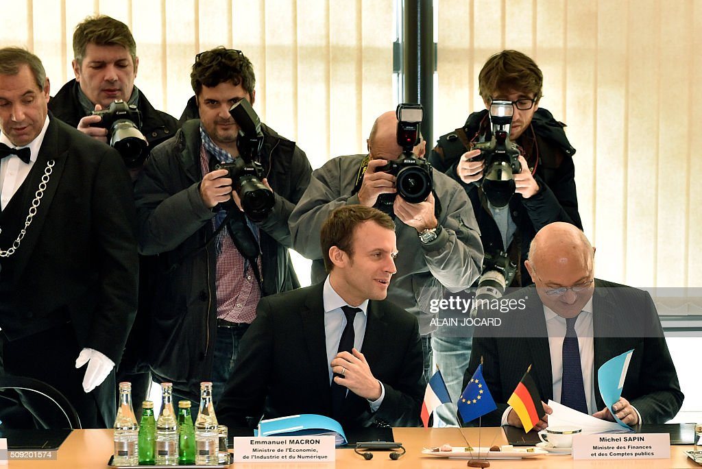 French Economy and Industry Minister Emmanuel Macron (L) sits next to French Finance Minister Michel Sapin (R), during the Franco-German Economic Council, on February 9, 2016, in Paris. / AFP / ALAIN JOCARD