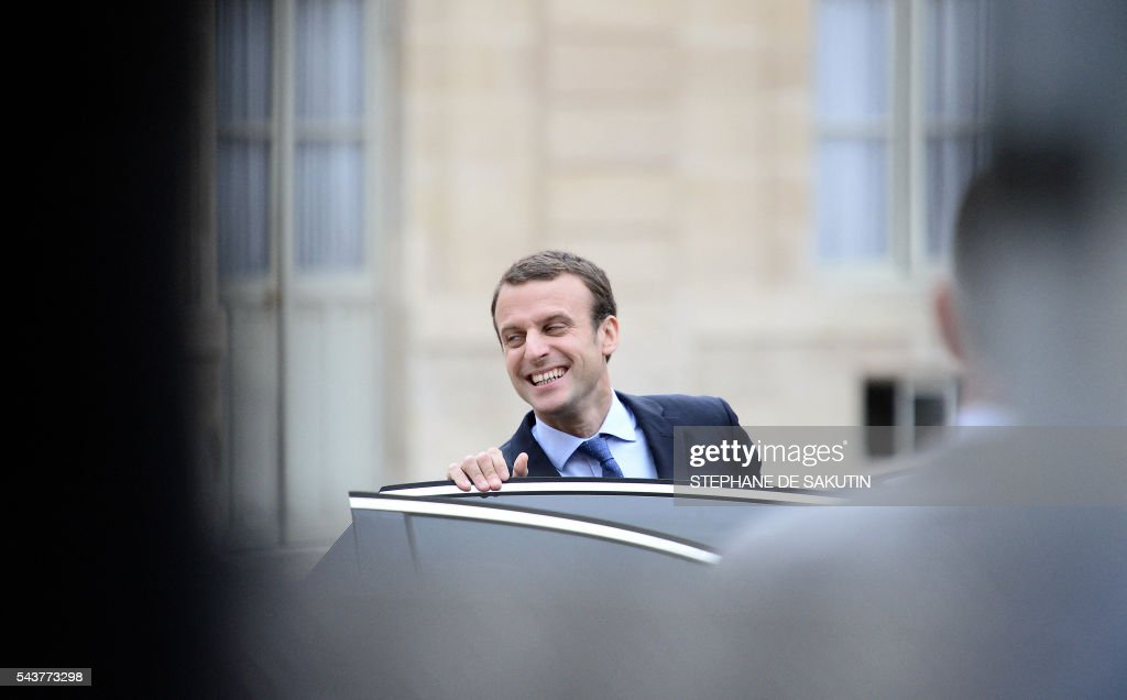 French Economy and Industry minister Emmanuel Macron smiles as he leaves after a weekly cabinet meeting on June 30, 2016 at the Elysee presidential Palace in Paris. / AFP / STEPHANE