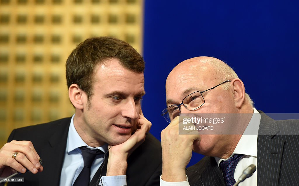 French Economy and Industry minister Emmanuel Macron (L) speaks to French Finance Minister Michel Sapin during the Franco-German Economic Council, on February 9, 2016, in Paris. / AFP / ALAIN JOCARD