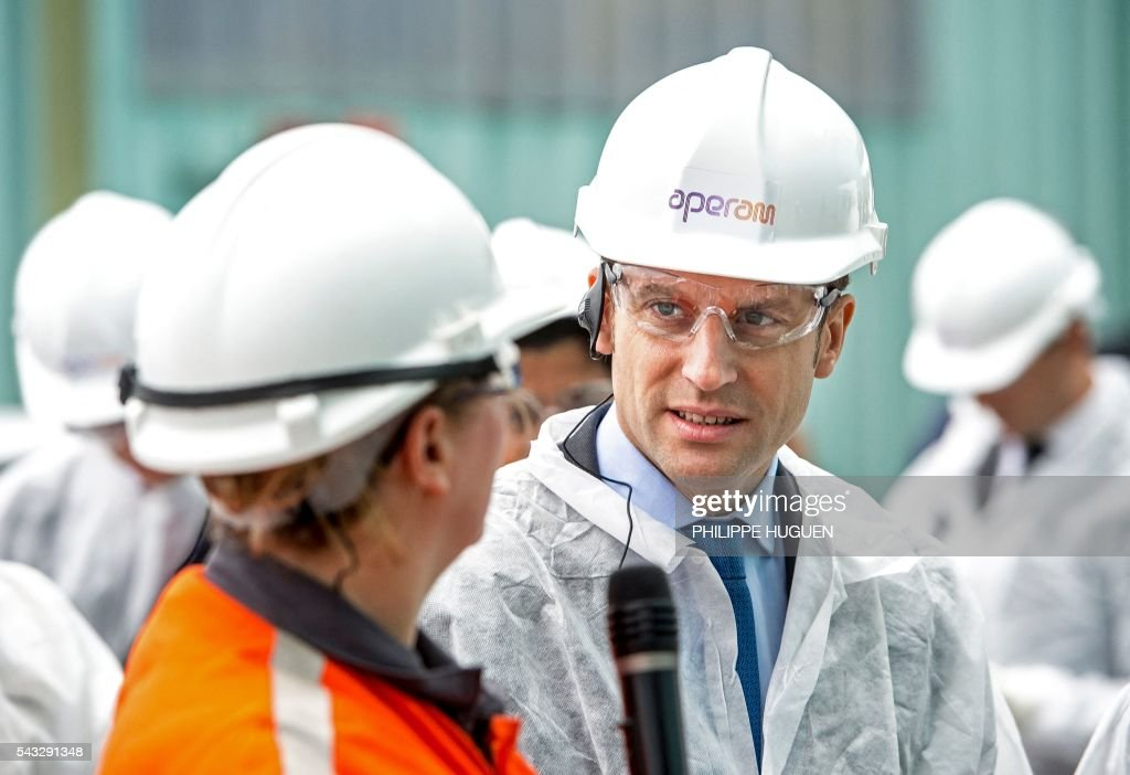 French Economy and Industry minister Emmanuel Macron wears a protection helmet as he visits Aperam's stainless facilities in Isbergues, northern France, on June 27, 2016. / AFP / PHILIPPE