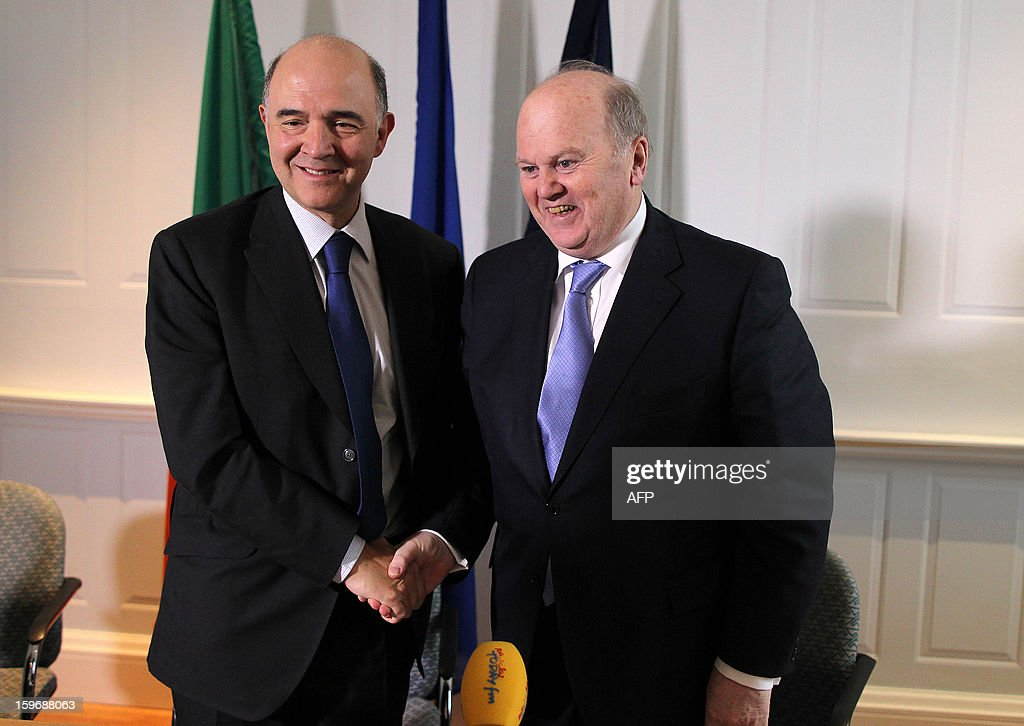 French Economy, Finance and Foreign Trade Minister Pierre Moscovici (L) shakes hands with his Irish counterpart Michael Noonan after a press conference at the Finance Office in Dublin, Ireland on January 18, 2013.