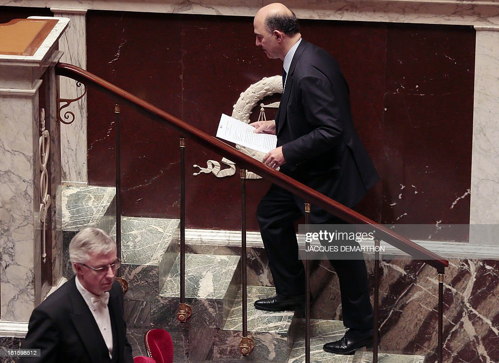 French Economy, Finance and Foreign Trade Minister, Pierre Moscovici climbs the stairs prior his speech about the bill on separation and regulation of banking activities on February 12, 2013 at the French National Assembly in Paris.
