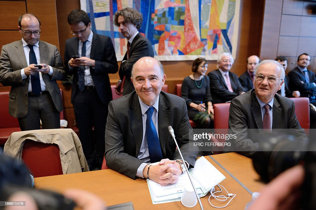 French Economy, Finance and Foreign Trade minister Pierre Moscovici (L) smiles on April 17, 2013 next to the president of the Financial commission at the National Assembly Gilles Carrez (UMP) at the beginning of his audition on the Cahuzac affair in Paris. French President Francois Hollande's government is scrambling to contain a scandal surrounding former budget minister Jerome Cahuzac, who was charged with tax fraud after admitting to having an undeclared Swiss bank account.