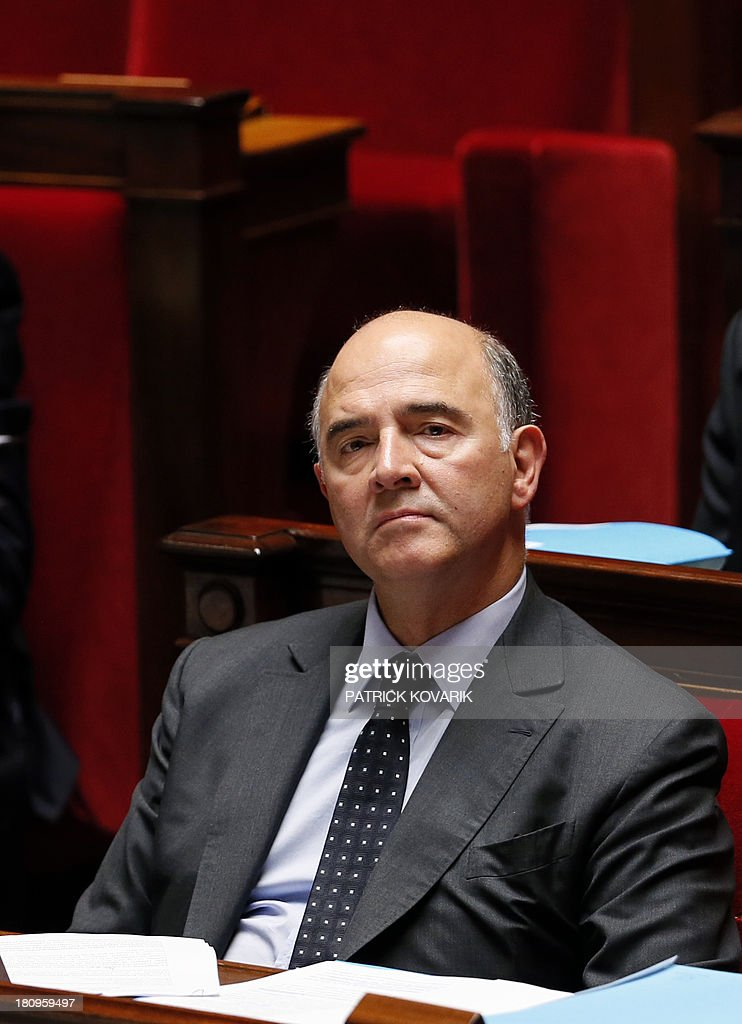 French Economy, Finance and Foreign Trade minister Pierre Moscovici listens during a debate at the National Assembly in Paris on a law aimed at putting pressure on companies leaving an industrial site unused to transfer the property and site to another company or the state, on September 18, 2013. AFP PHOTO / PATRICK KOVARIK