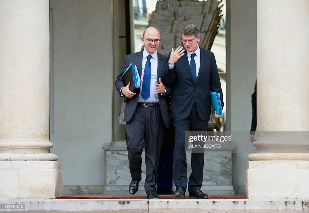 French Economy, Finance and Foreign Trade Minister Pierre Moscovici (L) and French Education Minister Vincent Peillon leave the Elysee Palace in Paris, after the weekly cabinet meeting, on November 6, 2013.