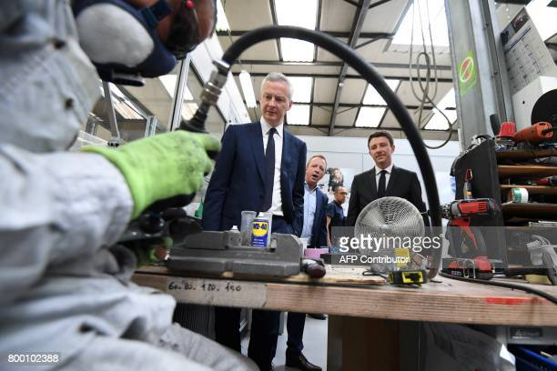French Economy Minister Bruno Le Maire and French Junior Economy Minister Benjamin Griveaux look at an employee working as they visit the ERPO SPRINT...