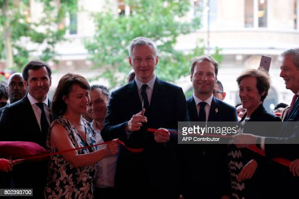 French Economy Minister Bruno Le Maire cuts the ribbon to launch the summer sales of a French department store in Paris on June 28 2017 / AFP PHOTO /...