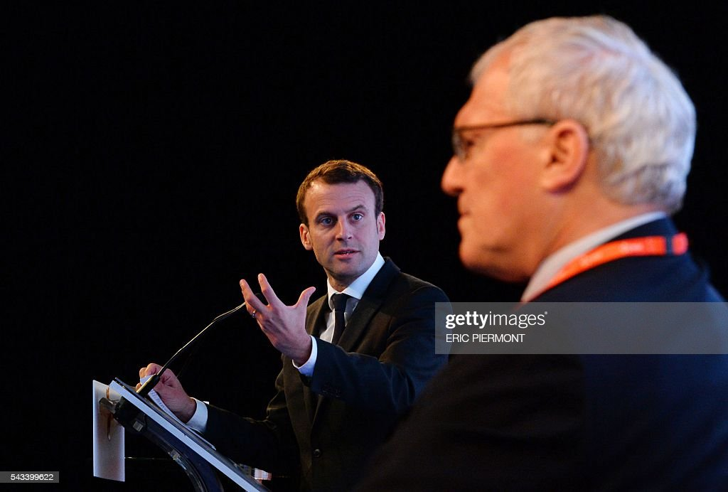 French Economy Minister Emmanuel Macron addresses the opening session of the World Nuclear Exhibition as France's state-run power firm EDF Chief Executive Jean-Bernard Levy listens in Le Bourget, near Paris, on June 28, 2016. / AFP / ERIC