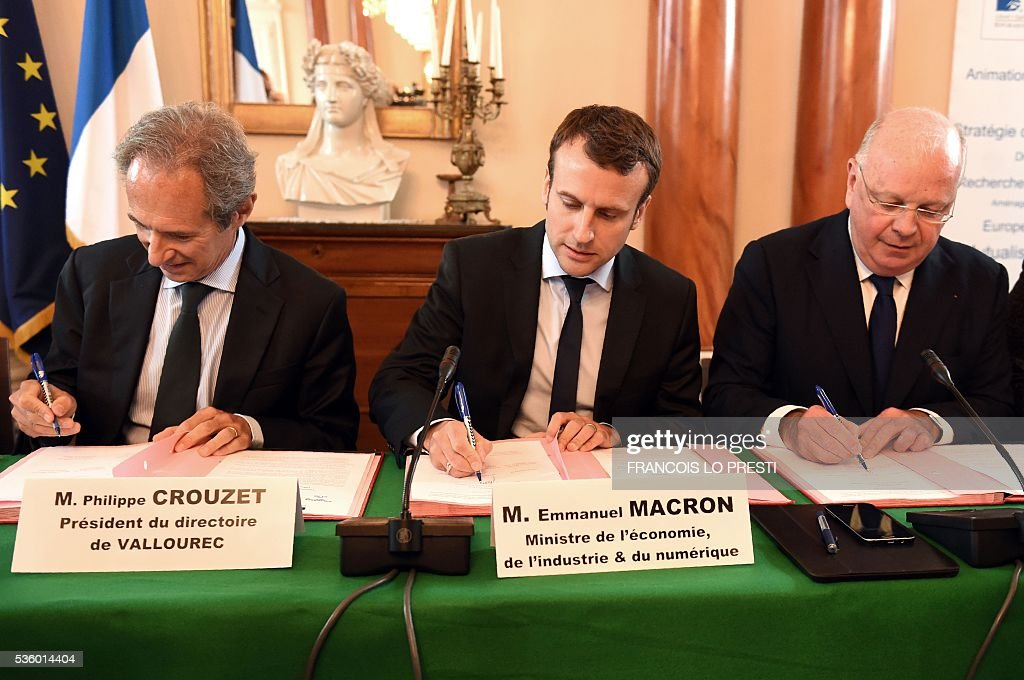 French Economy Minister Emmanuel Macron (C)and French steel group Vallourec chief executive Philippe Crouzet (L) sign an agreement on May 31, 2016 at the Valenciennes' sous-prefecture after a meeting on reindustrialisation in the North of France. / AFP / FRANCOIS