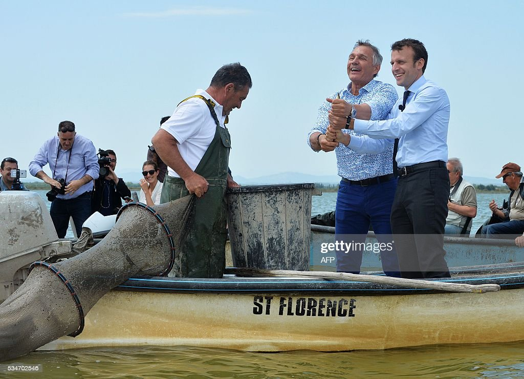 French Economy Minister Emmanuel Macron (R) and Herault MP Patrick Vignal (C) pose with caught eels on a motorboat on the lake of 'Etang de l'Or' on May 27, 2016. / AFP / SYLVAIN