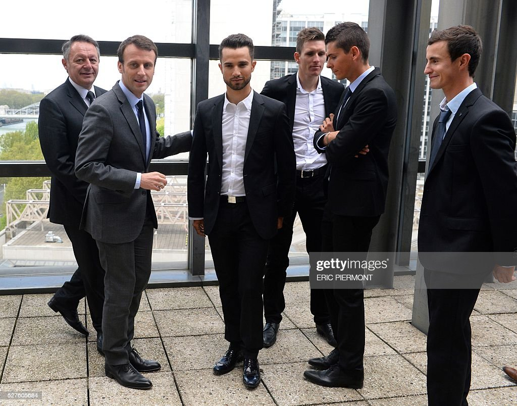 French Economy Minister Emmanuel Macron (2nd L) and Junior minister for Sports Thierry Braillard (L) stand next to French cyclists Nacer Bouhanni (C) Arnaud Demare (3rdR), Warren Barguil (2ndR) and Alexis Wuillermoz (R) while preparing for a picture prior to a meeting at the Economy Ministry in Paris on May 3, 2016. / AFP / ERIC